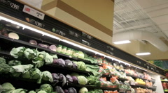 Buying produce in the aisle of a large grocery store Stock Footage