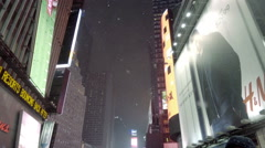 Tilting down from night sky and bright billboards Times Square ads snowing NYC Stock Footage