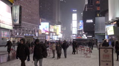 Tall ads and red picnic tables in middle of Times Square, snowing in cold winter Stock Footage