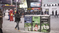 Throwing trash in garbage Times Square snowing in winter at night slow motion NY Stock Footage