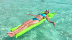 SLOW MOTION: Smiling woman laying and tanning on air raft Stock Footage