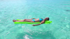 SLOW MOTION: Happy female laying and tanning on floating airbed Stock Footage