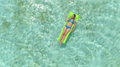 AERIAL CLOSEUP: Smiling woman swimming on inflatable air bed mattress - stock footage
