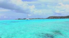 Yacht in beautiful crystal blue lagoon in Bora Bora island Stock Footage