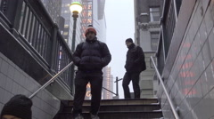snowing winter New Yorkers entering subway station staircase at 42nd st NYC - stock footage