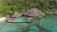 AERIAL: Luxury hotel resort with overwater villas and swimming pool - stock footage