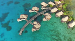AERIAL: Large luxurious overwater villas above the water in resort Stock Footage