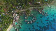 AERIAL: Flying high above luxury hotel resort with overwater villas Stock Footage