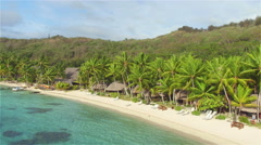 AERIAL: Secluded white sandy beach and lush palm trees paradise - stock footage