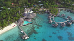AERIAL: Luxurious waterfront hotel resort on exotic white sandy beach - stock footage