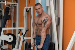 Bodybuilder Exercising Triceps - stock photo