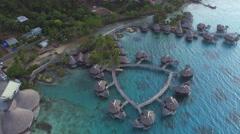 AERIAL: Luxury overwater bungalow villas in deluxe island hotel resort Stock Footage