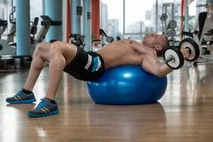 Dumbbell Incline Bench Press Workout On Fitness Ball - stock photo