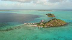 AERIAL: Flying around secluded island resort and luxury overwater villas Stock Footage
