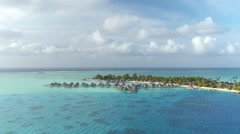 Flying around beautiful high class overwater villas at hotel resort Stock Footage