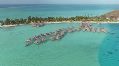 AERIAL: Luxury hotel resort with overwater bungalows and beachfront villas Stock Footage