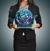 Young girl holding tablet in the hands of virtual digital globe Stock Photos