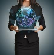Young girl holding tablet in the hands of virtual digital globe - stock photo