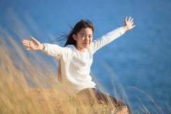 Portrait of asian girl relaxing emotion sitting in grass field and windy even Stock Photos