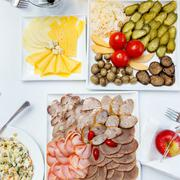 Cutting sausages, pickles and salads on a banquet table - stock photo