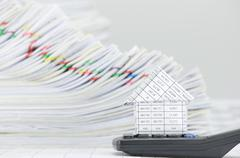 Stock Photo of Close up house on calculator have overload paperwork as background
