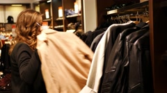 Women choose coat in a clothing store Stock Footage