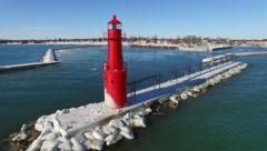 Aerial rotation view of beautiful red lighthouse in icy harbor Stock Footage