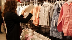 Pregnant woman choosing Baby Clothing in baby and maternity shop Stock Footage