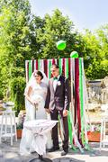 Newly married couple under wedding arch Stock Photos