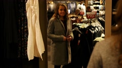 Female in clothes shop fitting on dress and looking in mirror - stock footage