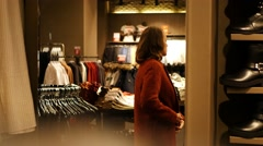Woman in store trying coat in mirror Stock Footage