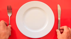 Hands Put Fork Knife at Right Angle on Plate on Red Table Stock Footage