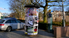 Advertising on a poster pillar covered with posters - stock footage