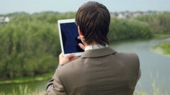 Young businessman standing on edge of rock mountain and using tablet pc. HD Stock Footage