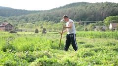 Man with scythe mowing high grass grown in the garden behind his house Stock Footage