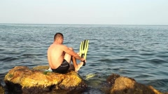 Man who is preparing to enter the sea. He puts his paws fish to swim faster - stock footage