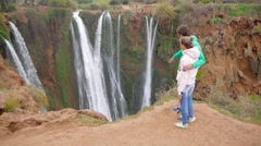 Woman and man looking waterfall. Filmed in Morocco near Ouzoud waterfall Stock Footage