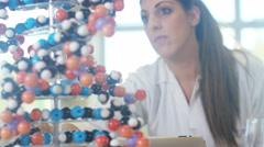 4K Teacher in science classroom looking at DNA model.  - stock footage