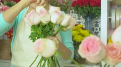 Flower shop, florist arranging pink rose bouquet - stock footage