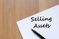 Selling assets write on notebook Stock Photos
