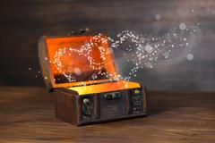 beautiful concept of retro chest with light heart miracle on wooden backgroun - stock photo