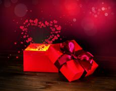 Greeting opened box with bow and miracle heart light on wooden background, St Stock Photos