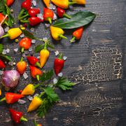 top down of yellow, red hot chili peppers, sea salt, greenery, black peppers  - stock photo