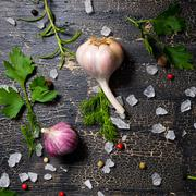 Stock Photo of top view of garlic, red, black peppers, sea salt, greenery on cracks black ba