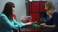 The girl chooses a color of nail Polish before manicure - stock footage