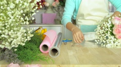 Flower shop, hand of florist wrapping cellophane around rose bouquet - stock footage