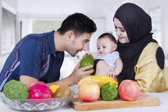 Arabian father giving fruit to his baby - stock photo