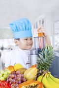 Child making juice of carrot and fruits - stock photo