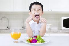 Child with thumbs up and vegetables salad - stock photo