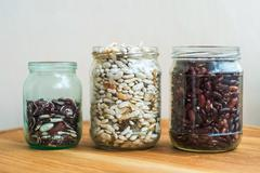Three kind of sorts of beans in glass jars. Assortment of seeds. - stock photo